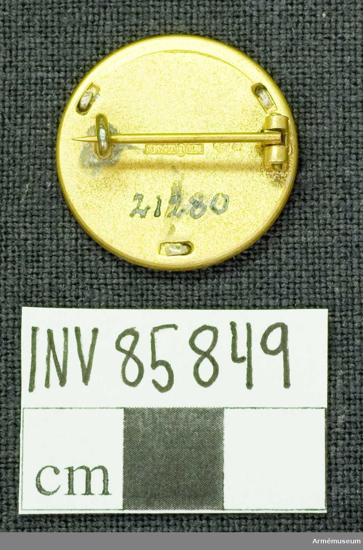 Grupp: M.      Lika med AM.085848 med den skillnad att kransen är utförd i silver samt att frånsidan är märkt S(?)(?), silverkontroll och M8.