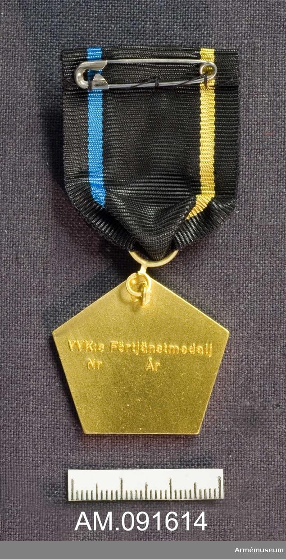 """Fodral innehållande Medalj samt släpspänne. Väg-och Vattenbyggnadskårens förtjänstmedalj, VVKGM. Femkantig. Märkt på framsidan med vapen och texten: """"VVK"""". Märkt på baksidan med texten: """"VVK:s Förtjänstmedalj Nr År"""". Band i svart med ett gult streck på ena sidan och ett blått på den andra."""