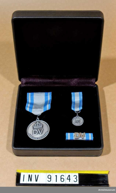 Etui innehållande medalj i silver, minimedalj samt släpspänne.  På medaljernas framsida finns text samt en kunglig krona. På baksidan endast text. Band i blått med brett grått streck i mitten och ett grått streck på vardera sidan.