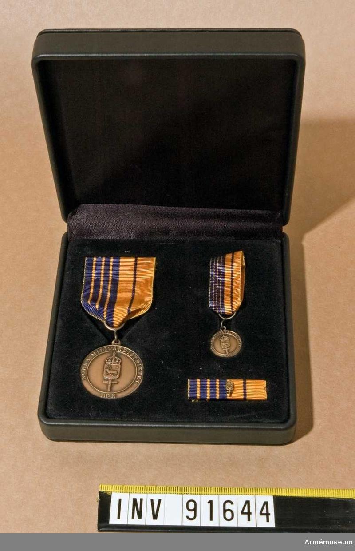 Etui innehållande Medalj i brons, minimedalj samt släpspänne. På framsidan ett vapen och text, på baksidan endast text.   Band i orange med fyra breda ränder i blått på ena hälften och en tunn rand i blått på den andra hälften.