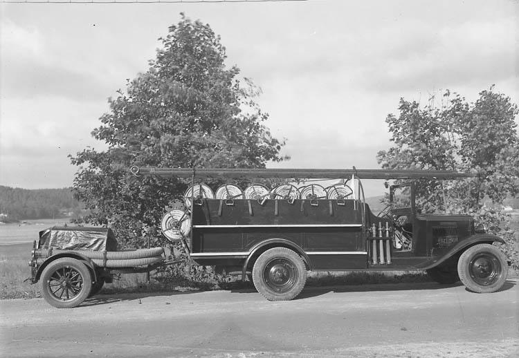 """Text till bilden:""""Brandbil på en grusväg med stegar, slangar och en släpvagn. Ljungskiles första brandbil""""."""