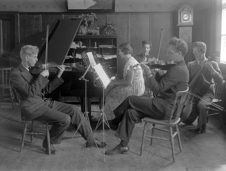 """Text till bilden:""""Orkester består av en dam på flygel, Herrarna spelar fiol, basfiol och klarinett. V. U. skolan 1933-34""""."""