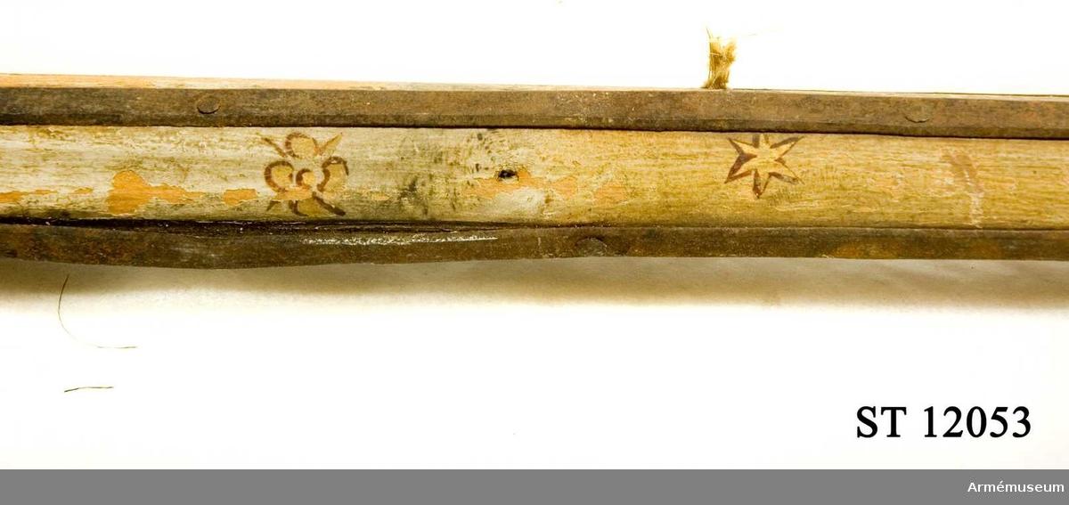 Stång av furu, vitmålad med små stjärnor och blommor i guld. Rester av duk i vit sidendamast. Förgylda tännlikor.  Etikett med text. No 6. Ryskt standar taget under konung Karl XII:s eget höga befäl 1704. Etikett från Riddarholmskyrkan No 898 M