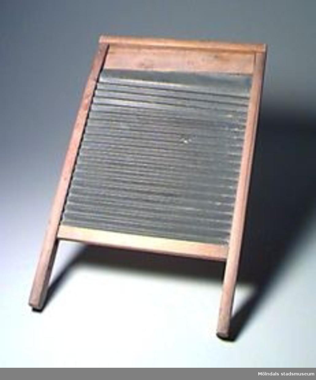 Tvättbräde, från 1900-tal. Valkbräde av zinkplåt. Mitt på plåten finns ett hål. Grön färgfläck.Tvättbrädet användes som så, att den våta tvätten gnuggades mot brädets ojämna yta för att få bort smuts.