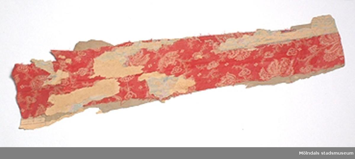 Ett persiskt blommönster (?) i rött. Textilfragment som suttit emellan två papperstapeter. Den ena tapeten är av Swedish grace-karaktär vanlig på 20-talet. Den andra tapeten är förmodligen från 30-talet eller senare.