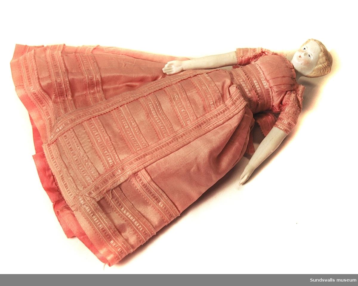 Flickdocka med huvud, hår, armar och ben av biskviporslin. Klädd i lång klänning av rosa siden.
