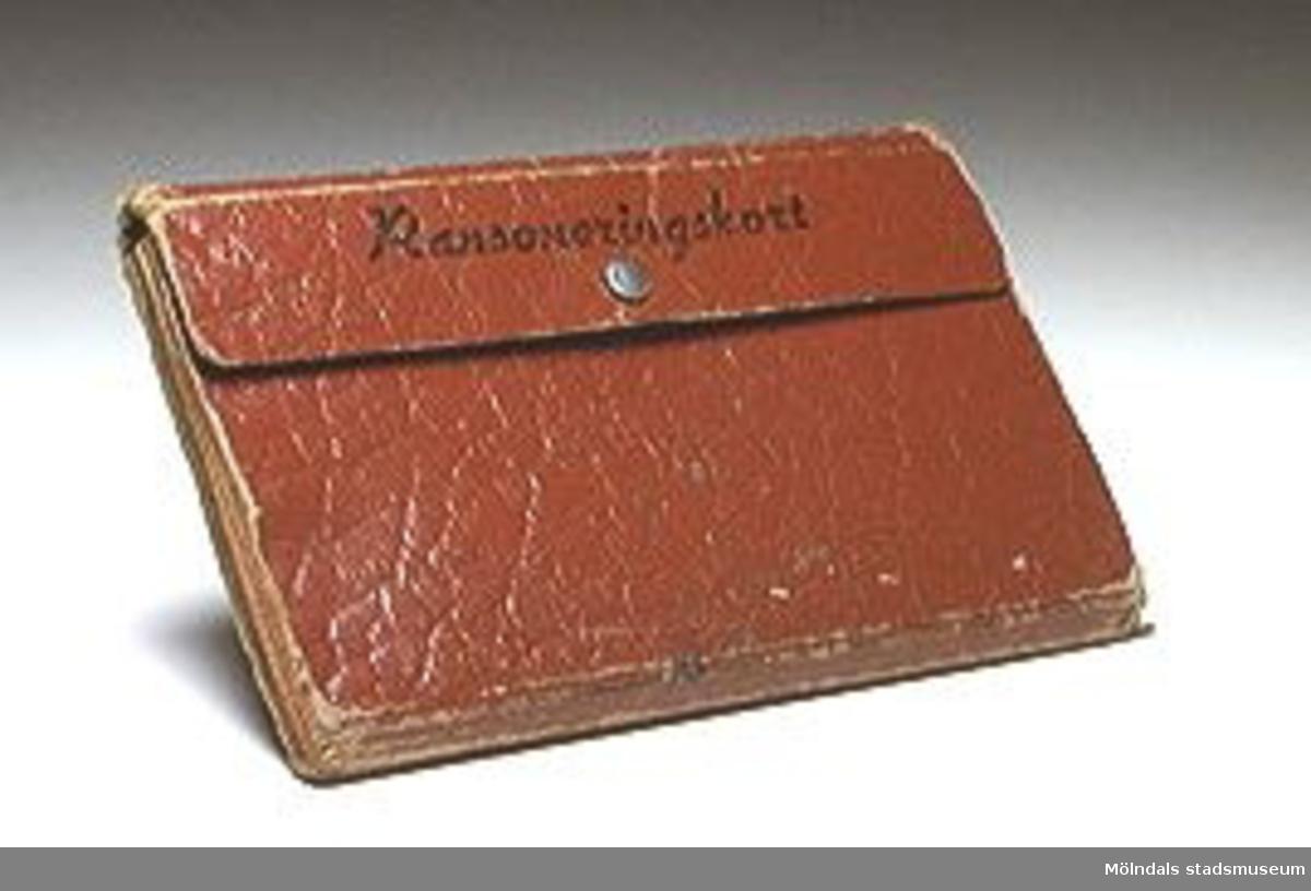 Mappens mått: L:168, B:108, H:12mm.I mappens 11 fack MM01676:1 ligger 15 st ransoneringskort:1 st kvitto för inlämning av ransoneringskort.2 st inköpskort för vete.2 st inkköpskort för kött, matfett, socker.6 st inköpskort för kaffe.1 st inköpskort för kakao, te.1 st inköpskort för ?1 st växlingskort för vete.1 räkning Yngeredsfors Kraft Aktiebolag.