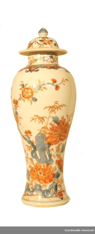 Vas med lock. Dekor föreställande en trädpion och fjäril i kinesisk imari. Rött och guld över underglasyrblått.