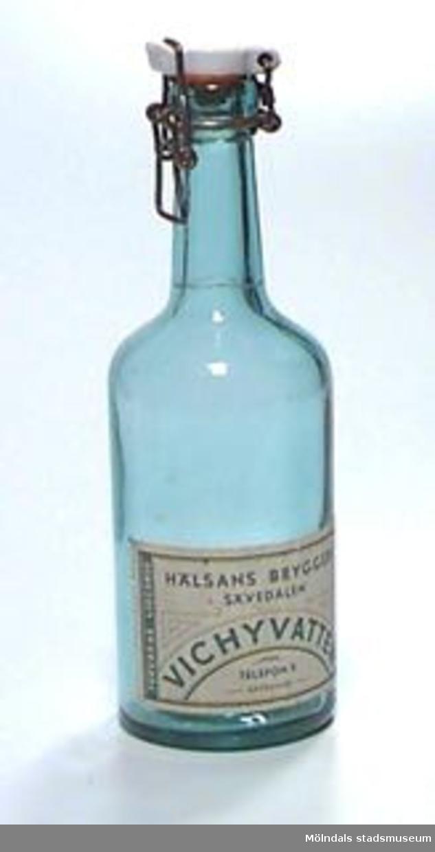 """Flaska i grönaktigt, men genomskinligt glas. Kork av porslin med ställning av grov järntråd. Gummit mellan kork och flaska håller på att torka sönder.I relief i glaset: """"ÅRNÄS 35"""". På etiketten står: """"HÄLSANS BRYGGERI/ SÄVEDALEN/VICHYVATTEN/ TELEFON 5 SÄVEDALEN/ FÖRVARAS LIGGANDE"""".Tidigare sakord: flaska med kork.Tidigare specialbenämning: vichyvattensflaska."""