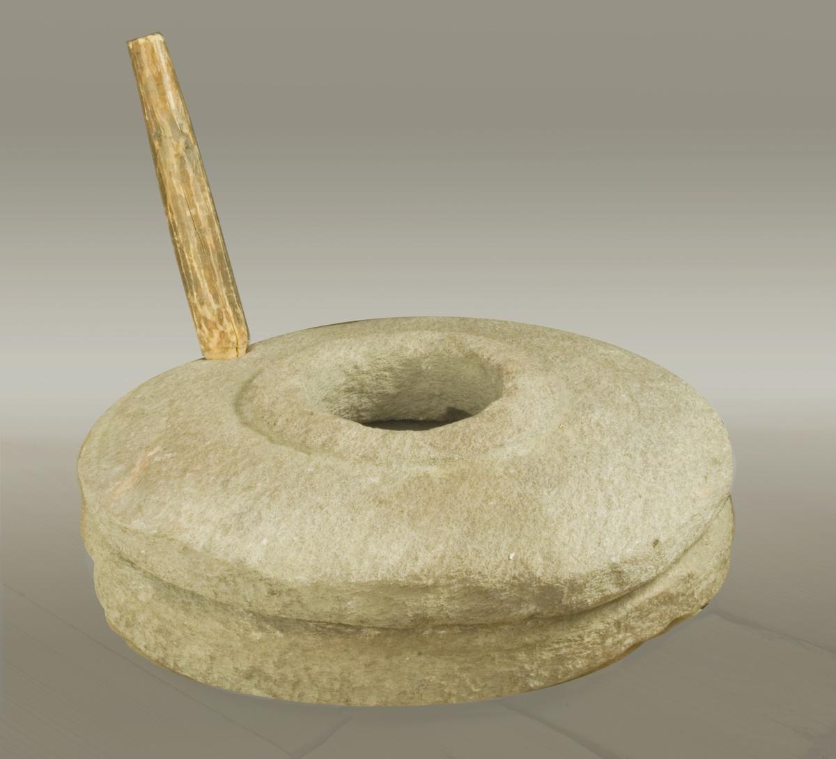 Handkvarn, med underdel och överdel, handhuggen av sten. Underdelen med mitthål, som nu är igenfyllt av något som liknar lera. Överdelen med mitthål samt hål nära kanten avsett för handtag av trä. Runt mitthålet en bred förstärkande upphöjd kant. Mitthålets diameter 140 mm.