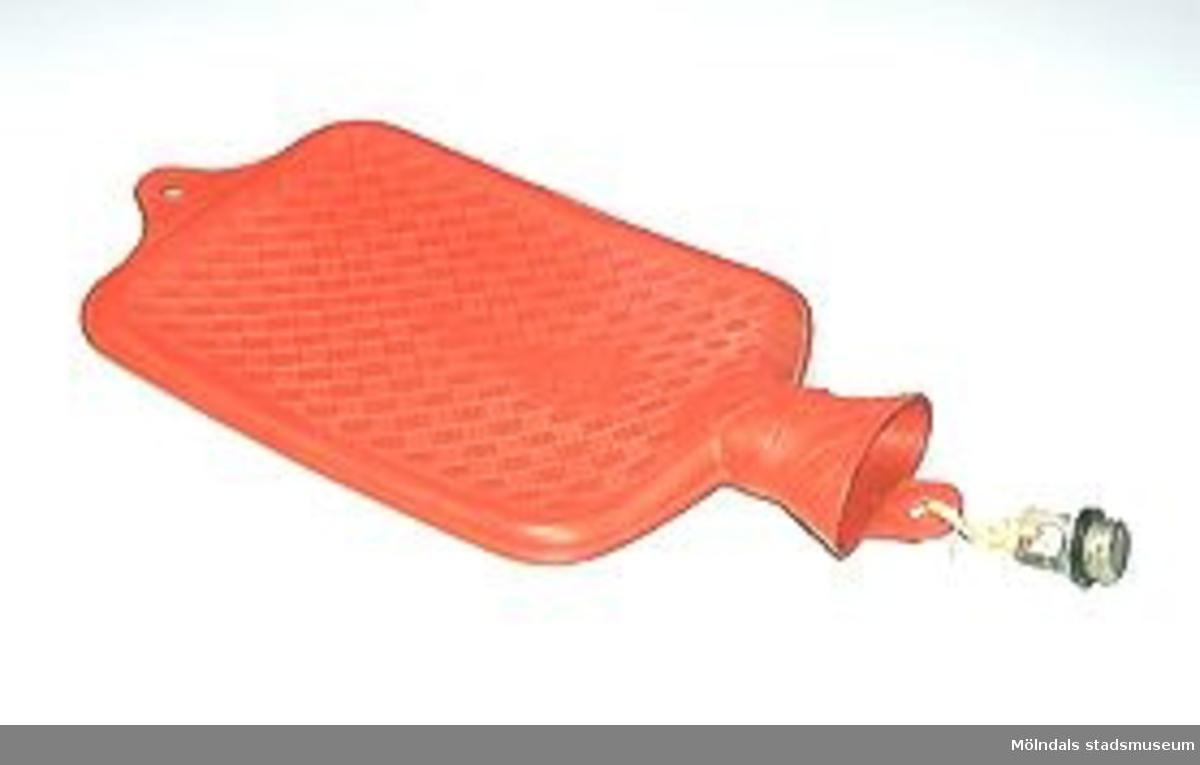 Varmvattenflaska av rött gummi. Rutmönstrade sidor. Skruvkork av metall. Volym ca 2 liter enligt tillverkaren.Otät, sprucken.Gåvan förmedlad genom Staffan Bjerrhede.