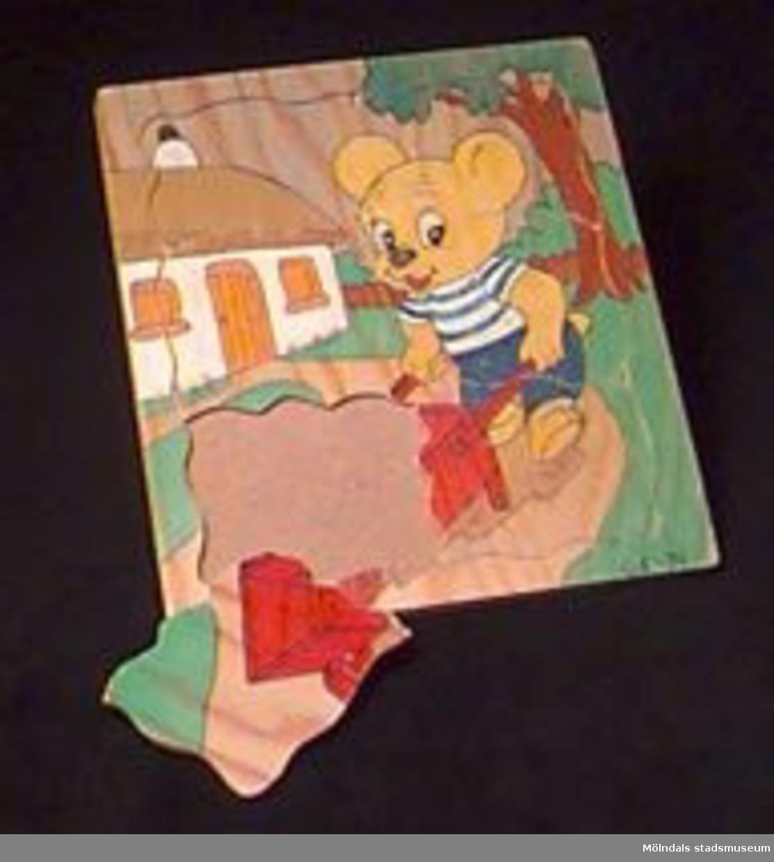 Pussel av sex bitar (samma typ som MM02344). Motiv: En i byxor och tröja klädd liten björn skjuter en tom skottkärra förbi ett vitt hus med halmtak. Pusslet verkar hemmagjort. Kanske av daghemspersonal. Signaturen tyder på att det är tillverkat 1974.Katrinebergs daghem var ett kollektivt daghem.
