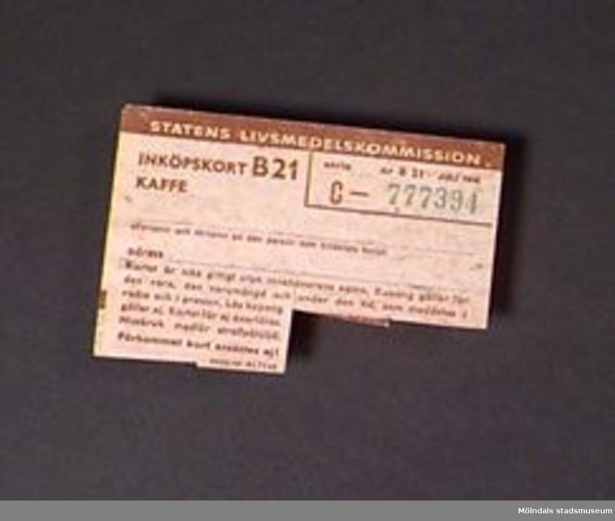 Ransoneringskort för kaffe. Pappret är gulbrunt och den tryckta texten är brun. Ett serienummer är tryckt i grön färg. Tillverkat för Statens livsmedels- kommission.