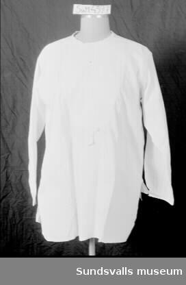 Vit skjorta med rund hals. Sprund i ryggen. Isatt bröststycke i mer arbetat tyg. Vidhängande lapp med texten 'Märta Moberg'.