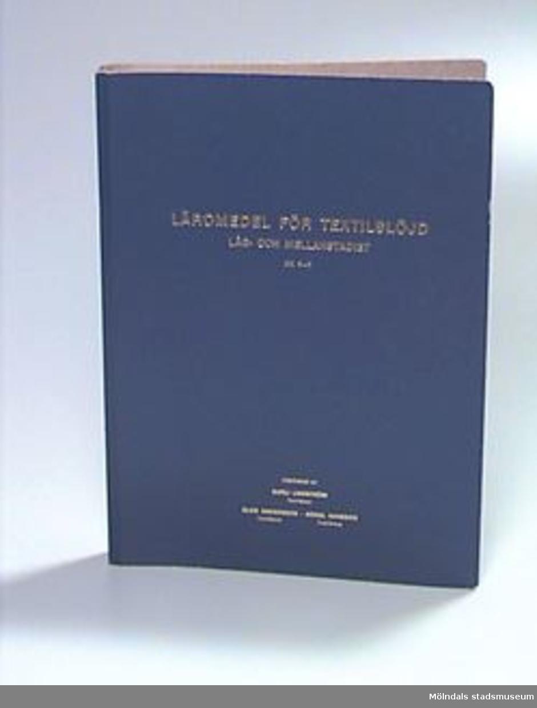 """Titel: """"Läromedel för textilslöjd"""". Blå pärm med undervisningsmaterial avsett för åk 3-6. Texten på pärmens utsida är guldfärgad. Birgit Ekstrands namn och adress på klisterlapp på insidan av omslaget. Övriga uppgifter se 02643:1."""