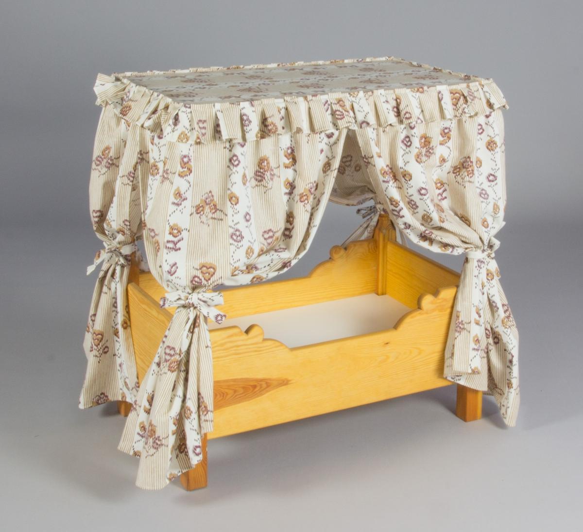 Sängklädsel till barnsäng  Tillverkad av vitt bomullstyg med tryckt mönster i mörkrött, strödda blombuketter av olika slag. Modell där främre och bakre förhänge är formsydda och fästa i ett överstycke, som vilar  på sängens överstycke. Klädseln är inte fäst vid sängen. Fast monterade omtag på främre förhängen. Veckad volang runt överdeln, kantad med band.