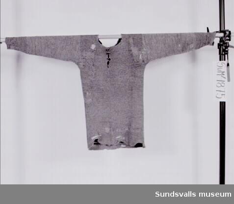 Stickad tröja i gråmelerat yllegarn. Kort knäppning fram med metallknappar vilka är märkta 'Solide Elegant'. Tröjan har lagningar med garn i andra färger.