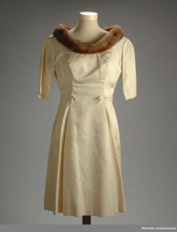 """En beige klänning med små fastsydda rosetter runt midjan """"50-årsstassen"""". Den har också en brun minkboa vid halsen.Det finns tillhörande kappa, schal, handväska och skor: invnr. MM03354:2, MM03354:3, MM03355, MM03356.Givarens egna noteringar: """"""""Stass"""" betyder ståt hade jag lärt från första barnkalaset 21 december. Mink runt dekolletaget hade jag bestämt redan på 49-årsdagen. Bästa presenten, mammas gamla välbehållna minkboa, visste den dagen sin plats runt halsen i min skiss över 50-årsstassen. I ateljé Marrigos syrum (Vasagatan) tråcklades halva boan på beige helsiden. Gröna kappan och långa fransschalen fodrades med beiga tyget. Beige och gröna sidenskor färgades hos Lagerssons skoaffär - ton i ton. Ståtliga Ordenshuset (Lennart Torstenssons gata) utgjorde en glansig festlokal för glänsande gäster kring """"ateljé Marrigos skapelse"""". """"Du är född under en lycklig stjärna, Margit""""; pappa-blinken åt minken i födelsedagstalet fick sin förklaring. Boan var pappas 50-årsgåva till sin fru en gång i tiden - att pryda strassiga födelsedagsstassen.""""Måtten:Längd 920 mm, bredd 460 mm (byst), armlängd 300 mm."""