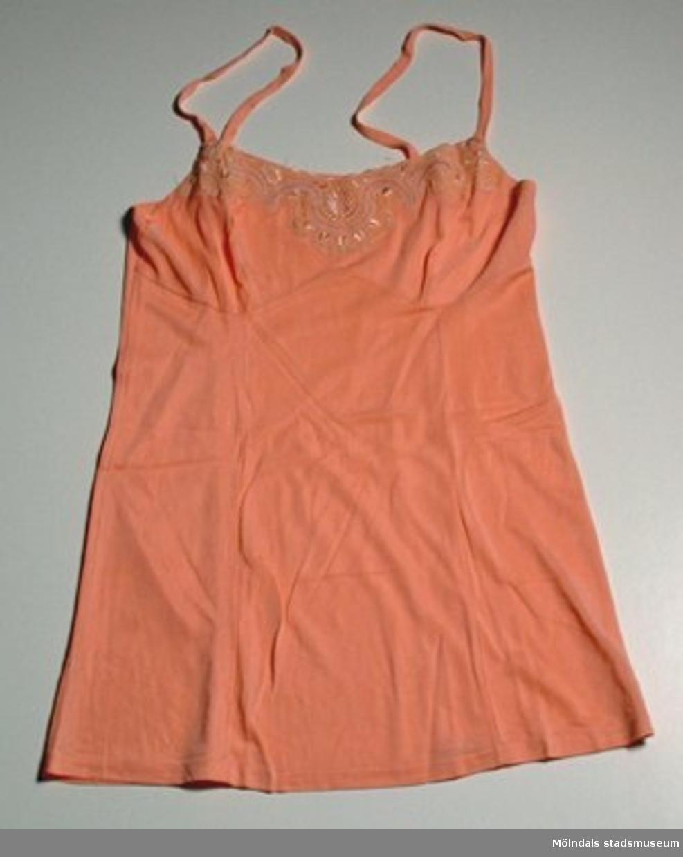 Ett linne, laxfärgat med brodyrspets, storlek 40 - ej använt.