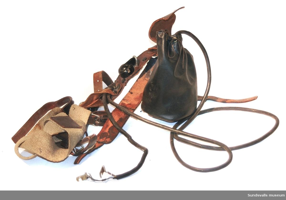Batteridriven handlykta med svart hårdplasthandtag. Har tidigare varit tillhörande en batteriväska i svart läder med dubbla spännremmar och bärsele i grov naturfiberväv och läder, vilken dock blivigt avlägsnad Framtill på selen sitter ett lampfodral av svart galon med lock och botten i läder. På selen sitter även en strömbrytare i svart hårdplast. Lampan var kopplad till ett batteriet med en gummiklädd sladd.