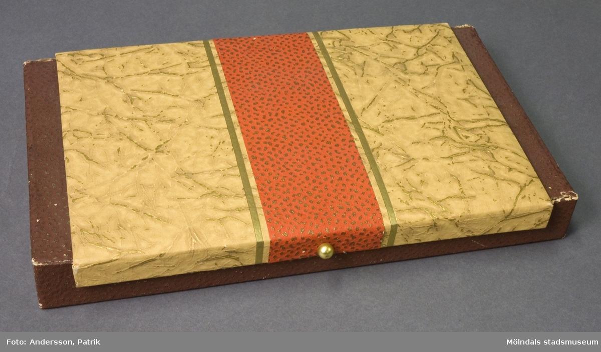 """Pappask med lock. Lådan är på insidan klädd i guldfärgat papper, på utsidan lila papper med guldprickar. Locket är klätt i beigt papper med prägling i oregelbundet mönster. Åsarna på präglingen är färgad med guldstänk. Tvärsöver locket går en röd pappersremsa med guldprickar. Fram på locket sitter en förgylld träkula, för att underlätta öppning. På undersidan sitter en liten etikett med handskrivet nummer: """"3846""""."""