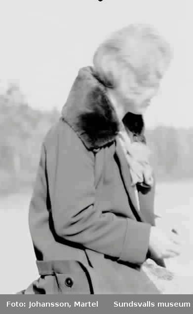 Kvinna iklädd kappa med skinnkrage.