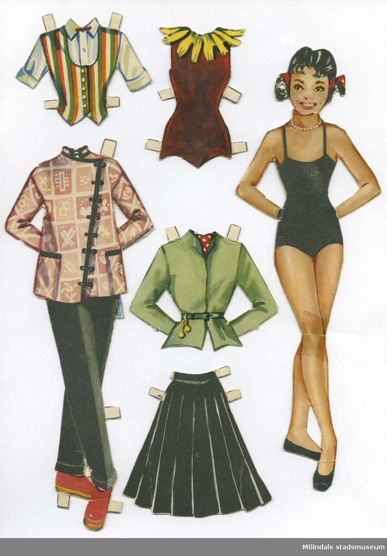 """Pappdocka med kläder från 1950-talet. Docka och kläder är märkta """"Margot"""" på baksidan - dockans namn.Dockan föreställer en ung kvinna med svart hår i tofsar, iklädd svart baddräkt och lågskor. Garderoben består av set med byxor och orientalisk jacka, toppar, kjolar, ballerinadräkt, östeuropeisk (?) folkdräkt, samt skor med snörning upp på smalbenet. Docka och kläder förvaras i ett brunt kuvert, märkt """"Margot"""", men är ursprungligen ett utgivarekorsband från Handelsnytt, Malmö."""