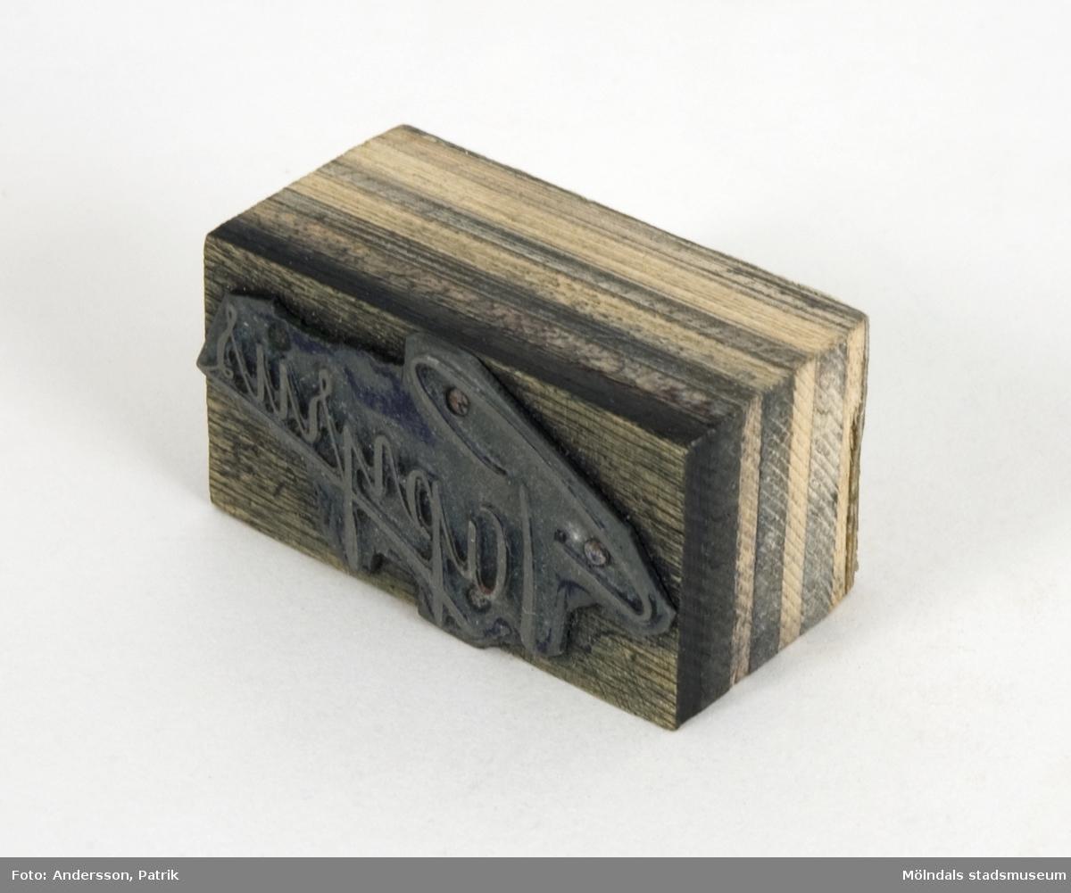 """Trycktyp av metall, monterad på träkloss, från Papyrus. Motivet på typen, är namnet """"Papyrus"""" i skrivstil. Motivet är spegelvänt för att det skall överföras rättvänt vid tryck på papper."""