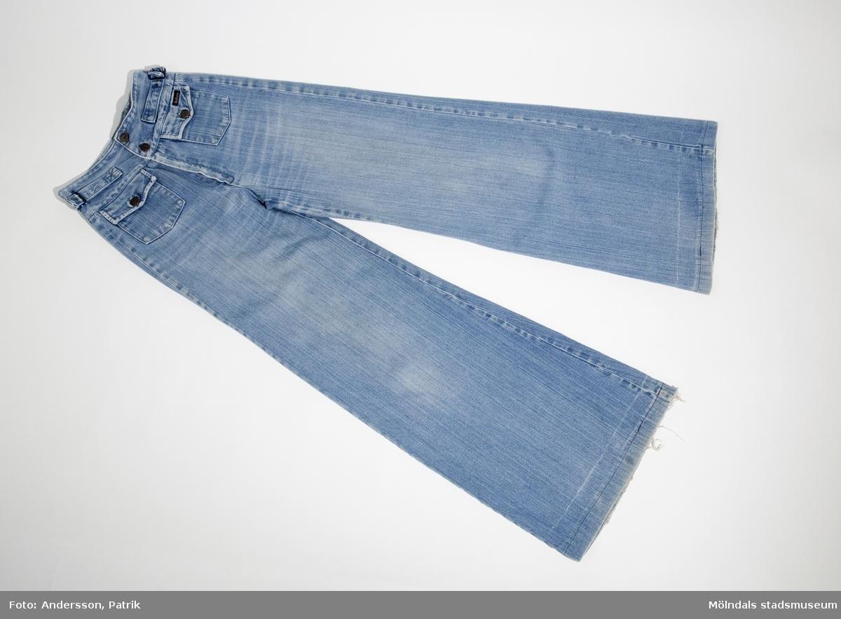 """Ett par blåjeans med hög midja och utsvängda. Dessa användes under 1970-talet.Byxorna har två fyrkantiga fickor med lock som knäppts med knappar, framtill. På vänster framficka är märket: """"Baboo"""" fastsytt. Byxorna har också två liknade fickor som bakfickor, där märket: """"Baboo"""" även är fastsytt på höger bakficka. Men detta är mycket slitet. I gylfen sitter en dragkedja och har två knappar i midjan som knäppning. I midjan sitter det också spänne på varje höft som prydnad.Byxbena är något slitna nedtill. Dragkedjan i gylfen är nog också något sliten eftersom det sitter en bortglömd säkerhetsnål där. MåttLängd: 1030 mm, Benlängd: 760 mm, Midjebredd: 295 mm."""