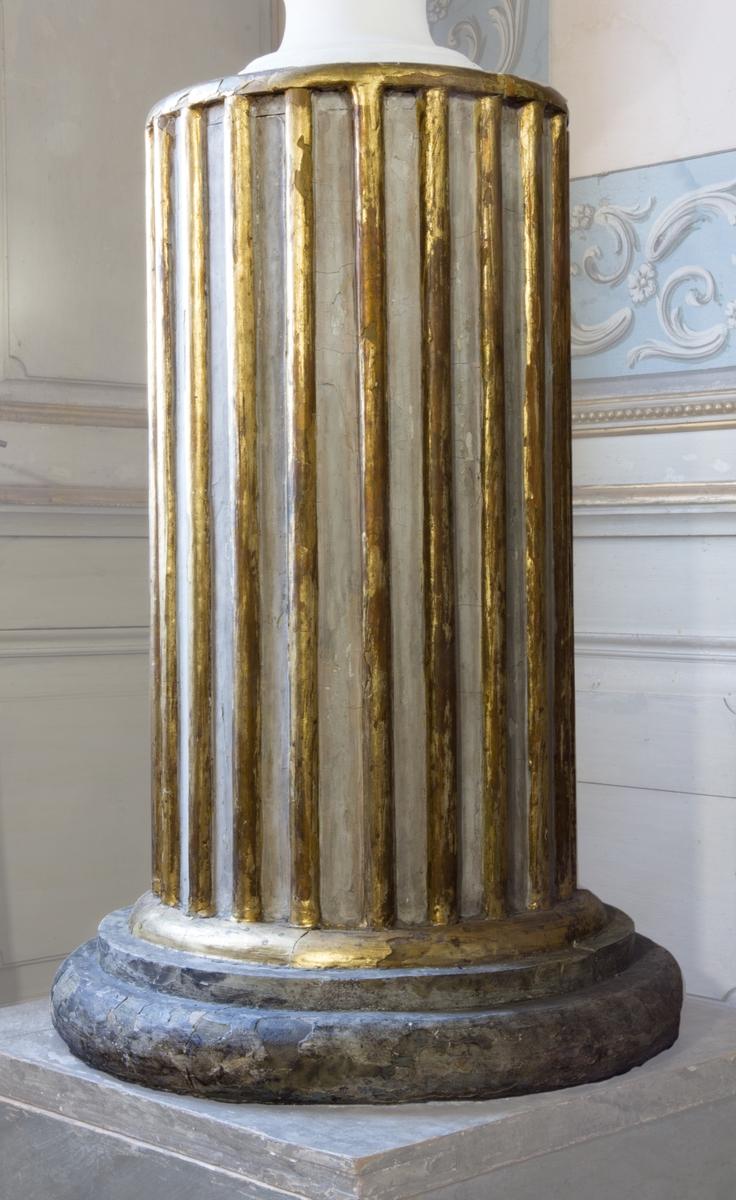 Piedestal av trä. Formad likt en kolonn på en rund stenbas. Kolonnen målad i vit med profilerade, skurna och förgyllda räfflor. Basen svarvad, skuren , skulpterad samt imitationsmålad för att likna sten. Underst en kvadratiskt skiva av trä, även den imitationsmålad.