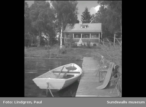 Gårdarna kring sjön. Kvinna vid öppna spisen, Sommarstugor, roddbåt vid brygga.