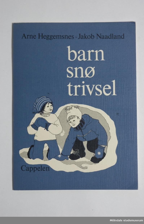 """Pärmarna är mörkblåa och ganska svåra att böja.Titeln """"Barn snö trivsel"""" (står på danska på boken) står i vit text ovanför en teckning av två barn som gör en snögrotta."""