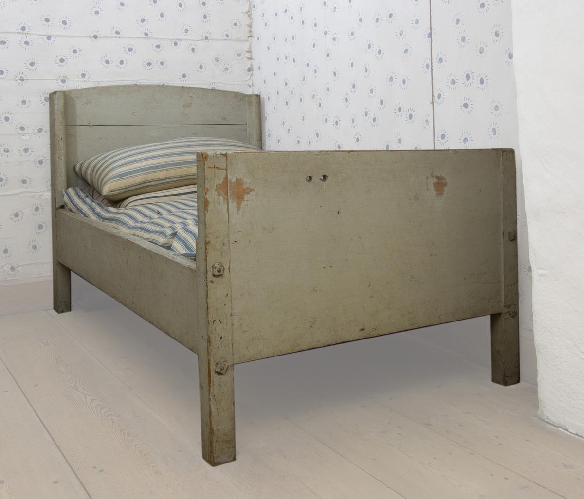 Säng i furu, enkel med hög, något rundad huvudgavel. Lägre, rak fotgavel. Målad i grågrönt.