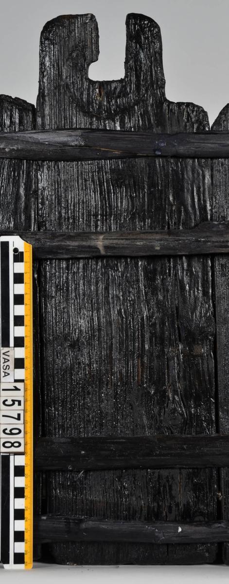 Laggstav till en balja. I stavens övre del finns ett urtag för en regel eller tvärslå. Urtaget är skadat och den övre delen saknas. Runt urtaget finns en fasad nedsänkning, eventuellt för någon form av beslag. På insidan av stavens nedre ände finns ett urtag. Urtaget är ett hugget spår där baljans bottenplatta sitter.