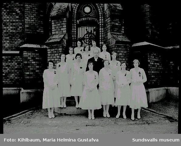 Grupporträtt framför Gustav Adolfs kyrka. Konfirmation, flickor och präst.