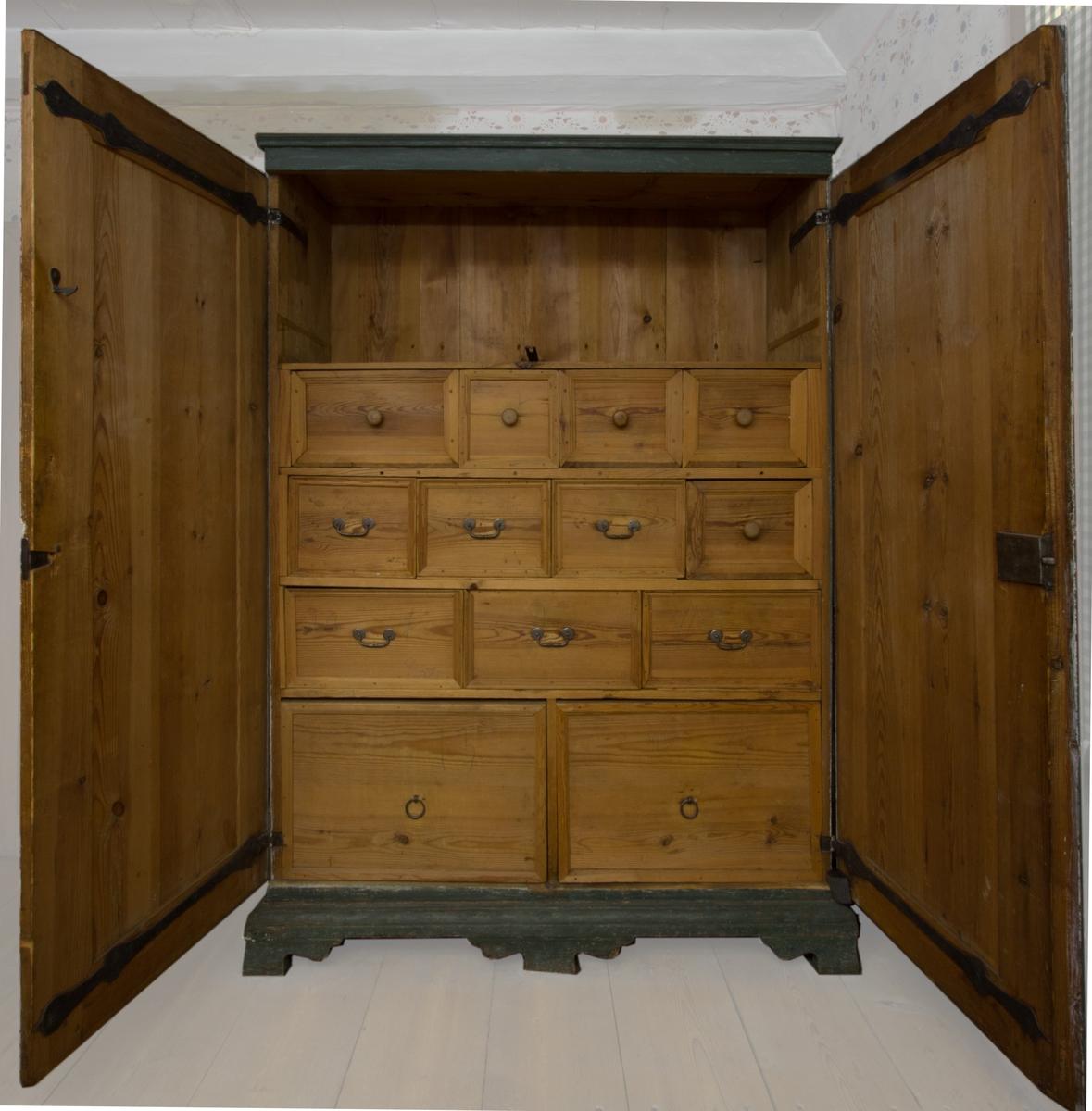 Kryddskåp, sannolikt furu. Dubbla spegeldörrar, fotställning med sniderier. Grönmålat med marmoreringar. Inuti ett flertal plan med olika stora utdragbara lådor. Handtag och ringar i järn, på några av lådorna träknoppar. Lås.
