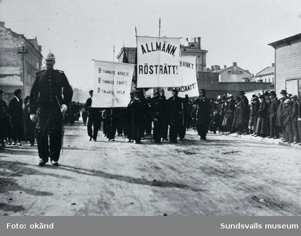 """Första maj-demonstratin för allmän rösträtt i Sundsvall 1899. Poliskonstapel """"Lång-Olle"""" till vänster."""