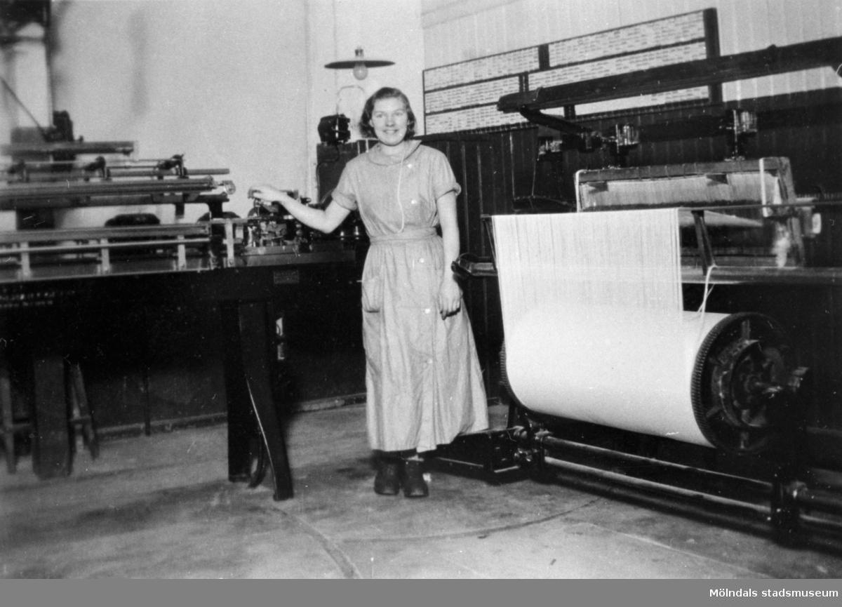 Karin Eliasson, syster till Anders Eliasson, står vid en knytmaskin.
