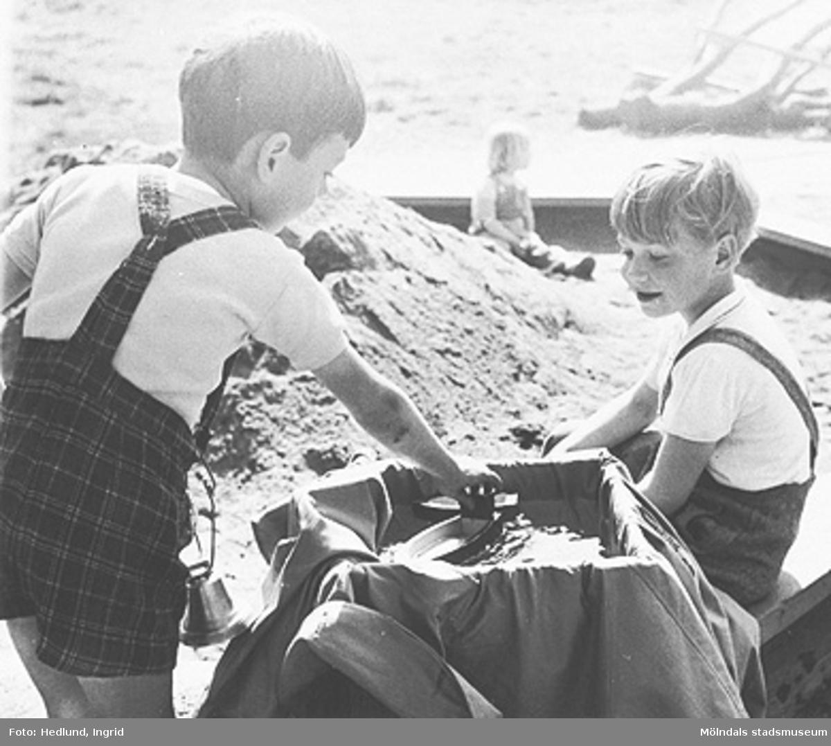 Två pojkar gör en vattenlek i sandlådan. Daghem i Guldheden, Göteborg. Sent 1940-tal.