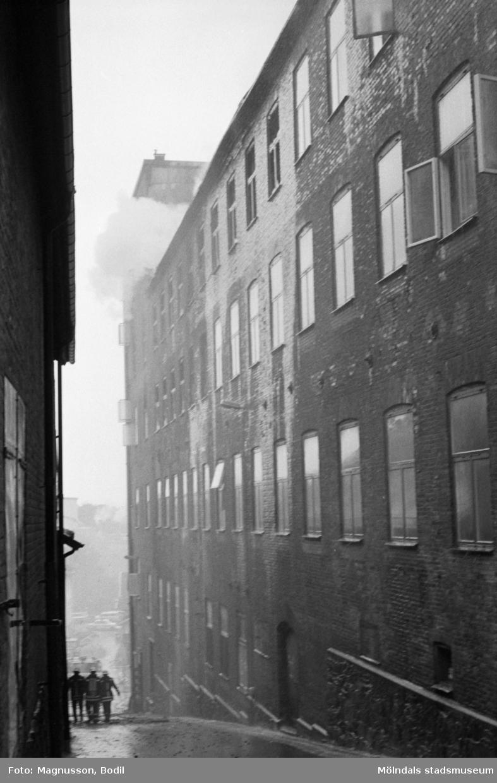 Soab-branden i Stora Götafors den 4 juni 1986. Tre brandmän går nedför Götaforsliden.