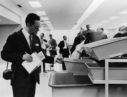 De fem nordiska postförvaltningarnas seminarium, för europeiska posttjänstemän inom ramen för CEPT, behandlade ämnet kassatjänst. Studiebesök på postkontoret Skärholmen 1 (som invigdes den 8 sept 1968).  Foto 5 sept 1968. Mr António Ramos, från Portugal, tittar intresserat på ett lådställ i brevkassan.