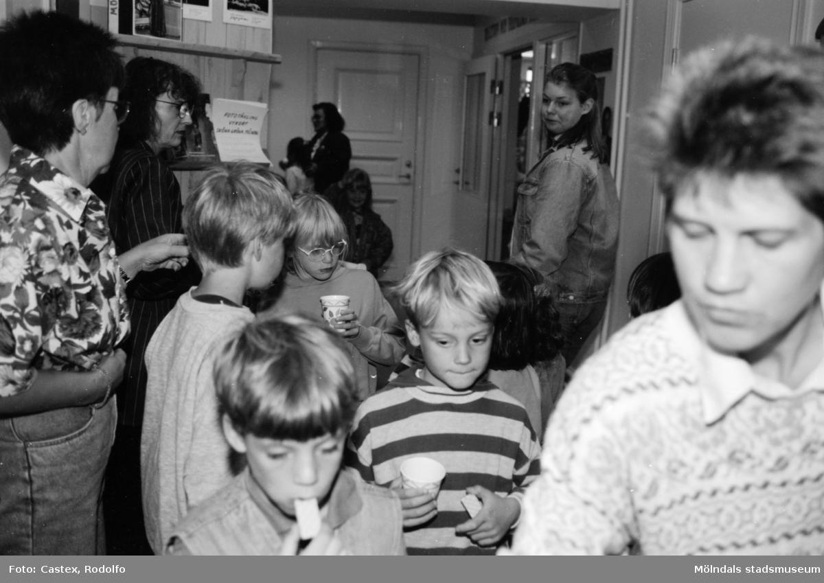 Barn och vuxna som står i entrén till Mölndals museum. Det är fikapaus och barnen dricker ur muggar eller äter kex. Utställningsvernissage av och om Katrinebergs daghem på Mölndals museum 1993-09-10.