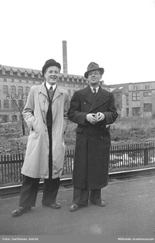 Charlie Jinnerstedt och vännen Helmer Garthman står på en väg, uppklädda i hatt och rock. I bakgrunden syns Almedals fabriker. Almedal (Göteborg), 1930.
