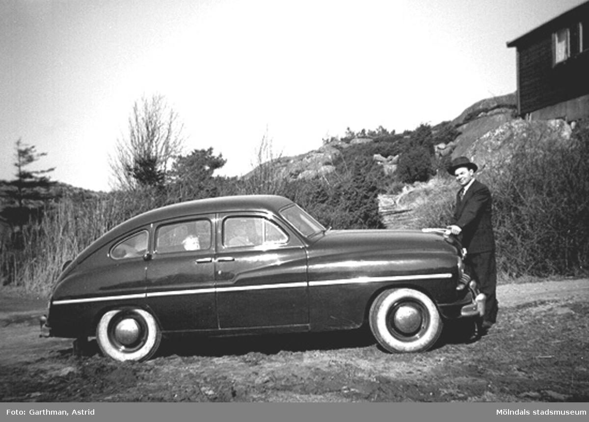 """Dimitri Koski står vid sin """"ögonsten"""" - en Ford Vedette. Alf Garthman sitter i baksätet i bilen. Näset, 1955."""