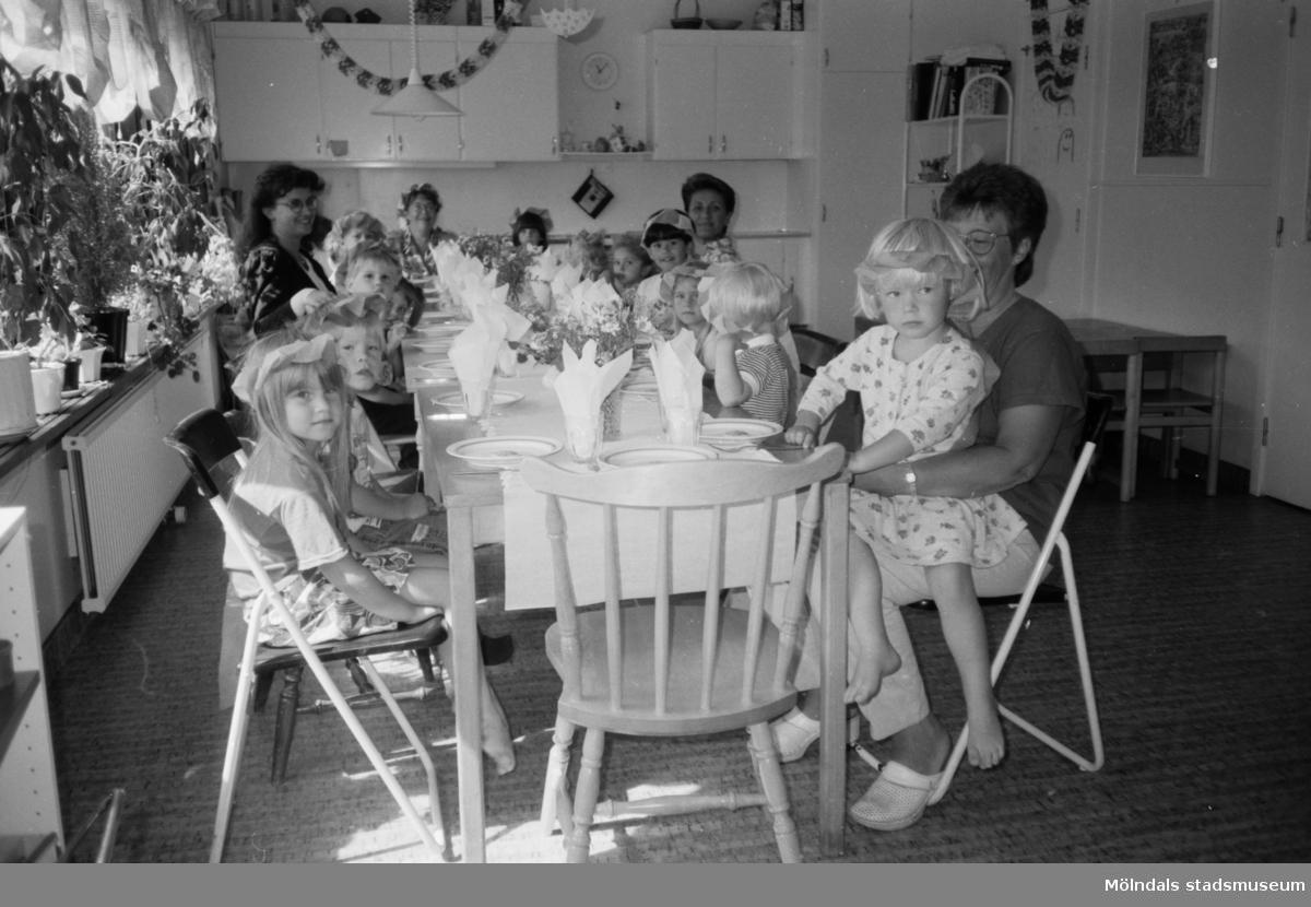 Midsommarfirande för barn och förskollärare som sitter inomhus i köket vid ett fint dukat bord. Barnen har kransar gjorda av papper i håret. Lunkentussen, Katrinebergs daghem 1992-93.