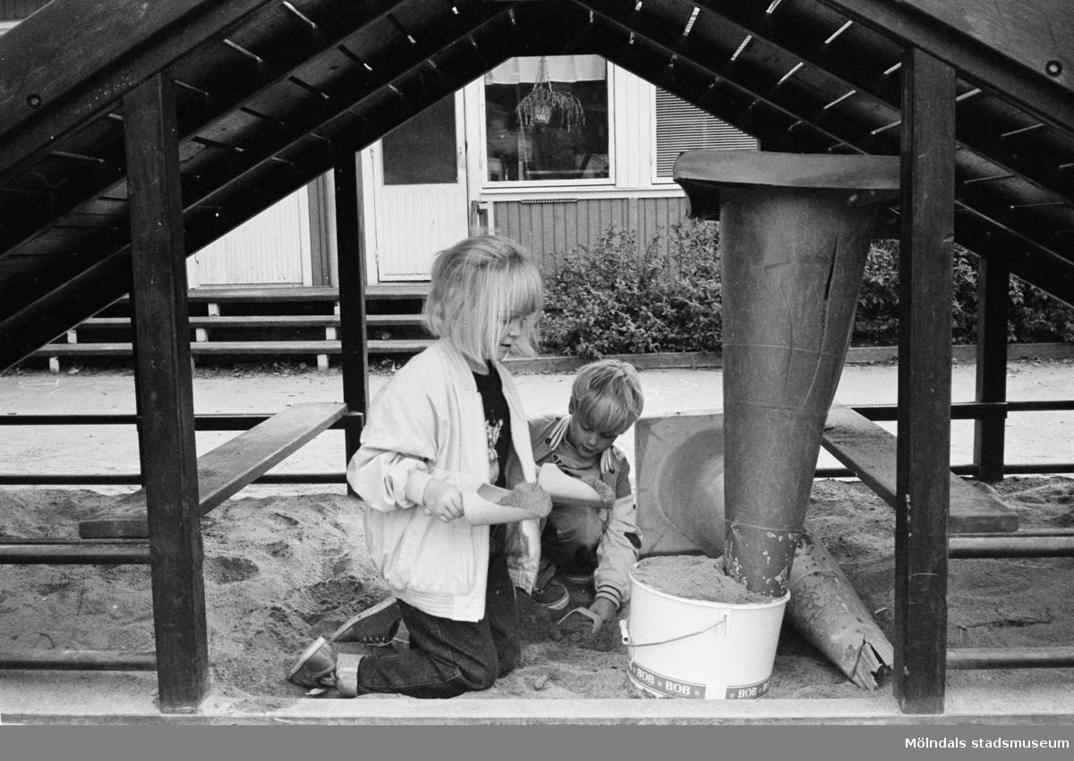 Anna-Maja och Mattias leker utomhus i en sandlåda. Båda har tagit skydd under en rutschkana som är byggd som ett litet trähus. De häller sand, dels i en plast-hink samt i en plast-kon som de har vänt uppochned. Hoppetossan, Katrinebergs daghem 1992.