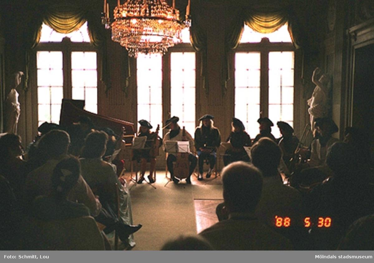 Människor som lyssnar till en konsert inomhus på Gunnebo slott. Personerna som spelar instrumenten är iklädda  historiserande dräkter. I bakgrunden ser man en flygel och i taket hänger en stor, pampig kristallkrona.