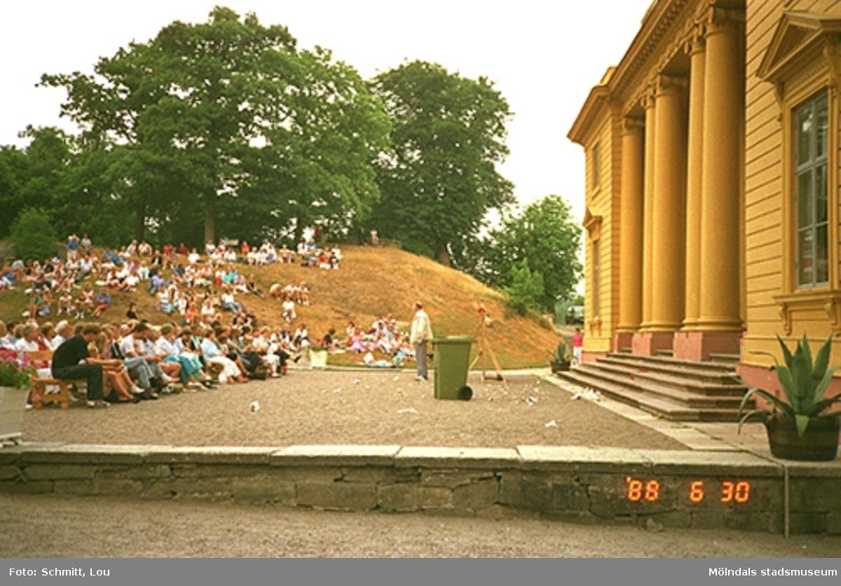 Människor som sitter och tittar på en teaterföreställning framför Gunnebo slottsentré. Till höger ser man en del av det gula slottet.