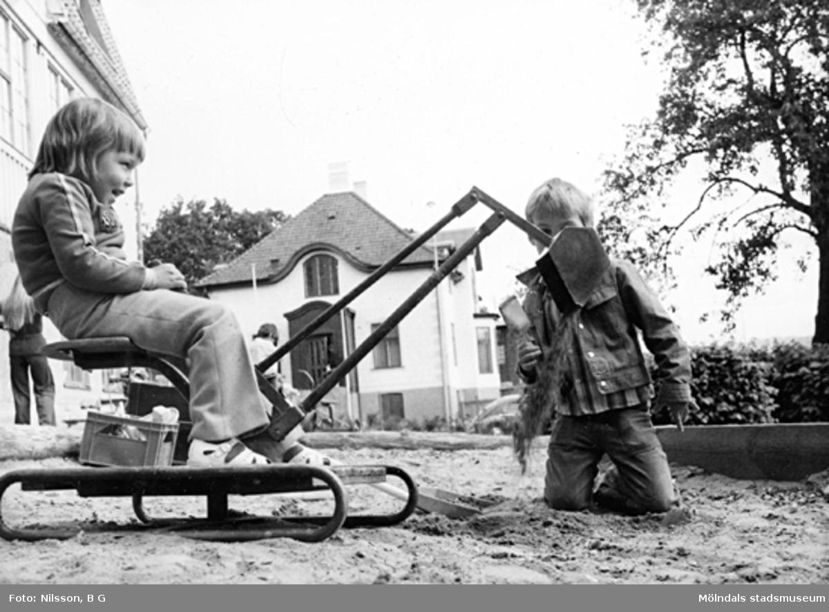 Två barn som leker med en grävskopa i sandlådan. Holtermanska daghemmet juni 1974.