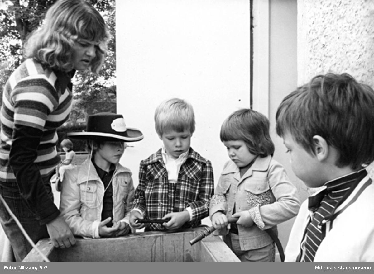 En fröken och fyra pojkar står samlade runt en behållare. Holtermanska daghemmet juni 1974.